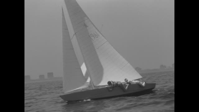 vidéos et rushes de good tracking shot of star-class yacht closest to camera catching up and passing other boat, crew members of closest boat hanging over the side to... - équipe de voile