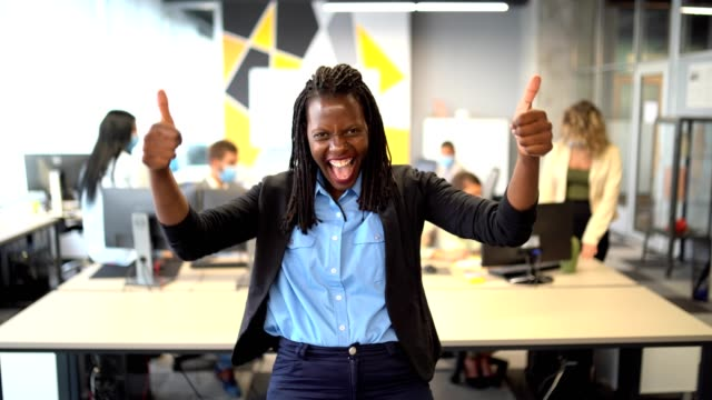 good work - excited team leader stands in her office in front of the colleagues and shows thumb up - thumb stock videos & royalty-free footage