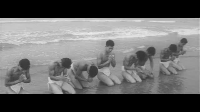goodbye ohitsu(boiled-rice boxes)/young men purifiying themselves at enshunada beach, start fire & cook red bean rice /straw, putting red bean rice... - 作法点の映像素材/bロール