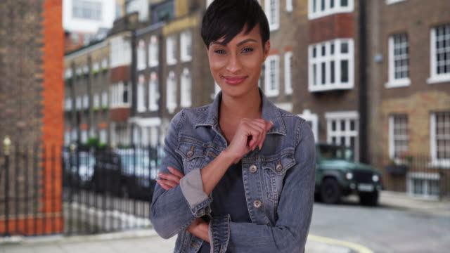 good-looking african-american female in london looks at camera happily - hüfte stock-videos und b-roll-filmmaterial