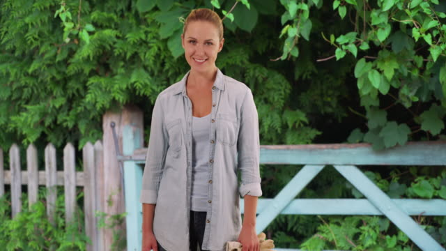 Good-looking Caucasian woman out gardening posing cheerfully by wooden fence