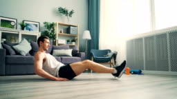 Good-looking man doing abdomen crunches different positions wearing sportswear