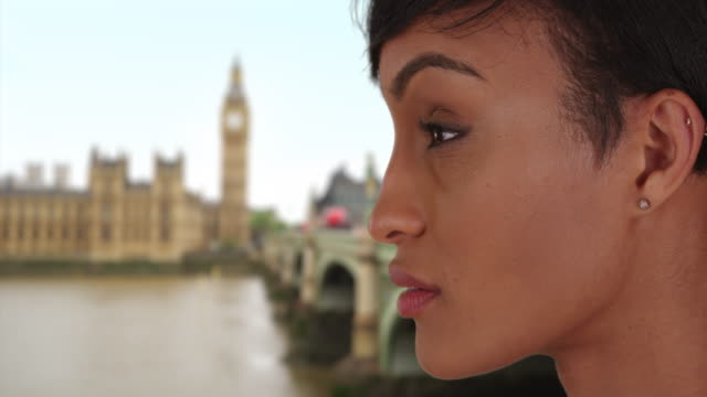 Good-looking mixed race female traveling in London turns and looks at camera