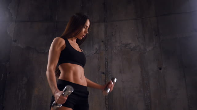 good-looking woman performing sport exercise with double dumbbells - bicep stock videos and b-roll footage