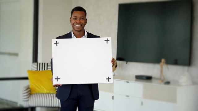 good-looking young businessman holds blank white sign indoors - poster stock videos & royalty-free footage