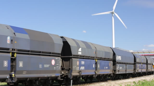 a goods train in amsterdam going past the docks with wind turbines - netherlands stock videos and b-roll footage