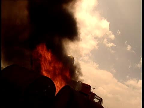 a goodyear airship passes above black smoke from burning barrels. - burning stock-videos und b-roll-filmmaterial