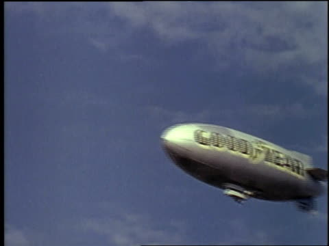 1957 LA Goodyear blimp flying past small aircraft / New York City, New York, United States