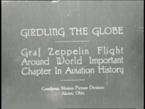 a goodyear film shows thousands of people walking under the giant blimps graf zeppelin and los angeles in a hangar in new jersey. - 飛行船点の映像素材/bロール