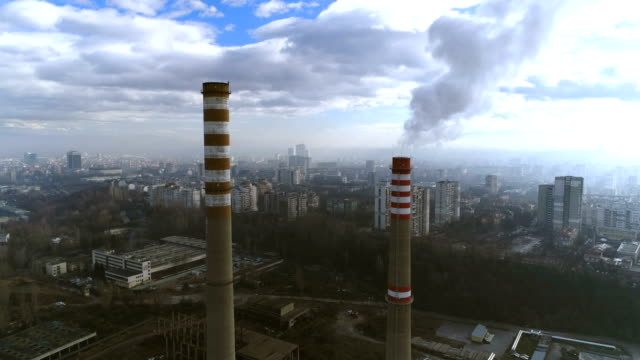 gorgeous aerial drone shot flying between two heavy industry factory chimneys - bulgaria video stock e b–roll