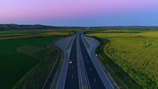 gorgeous aerial view drone flying over highway after sunset - horizon over land stock videos & royalty-free footage