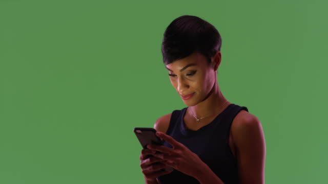 gorgeous african american female texting on smart phone on green screen - silhouette stock videos & royalty-free footage