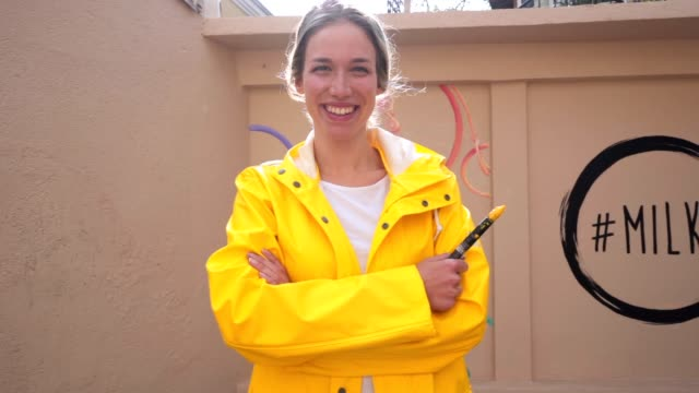 Gorgeous and smiling artistic girl in a yellow raincoat holding a paintbrush