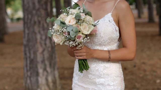 wunderschöne blumenstrauß in den händen der charmanten braut in einem weißen kleid - weißes kleid stock-videos und b-roll-filmmaterial