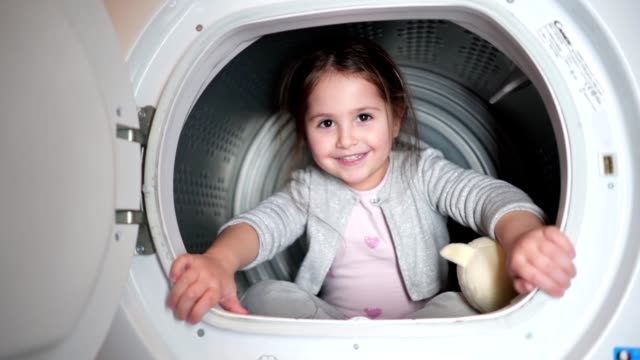 gorgeous carefree child having fun sitting in a washing machine - tumble dryer stock videos & royalty-free footage