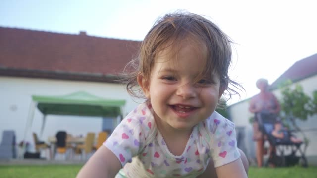 gorgeous cheerful baby girl crawling on grass in the back yard - babies only stock videos & royalty-free footage