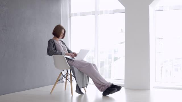 Prachtige kastanje vrouw zittend op een stoel en die op laptop werkt