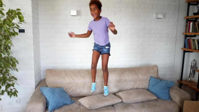 gorgeous child jumping on a sofa at home - messy stock videos & royalty-free footage
