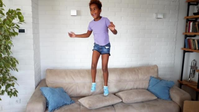 vídeos de stock, filmes e b-roll de linda criança pulando em um sofá em casa - messy