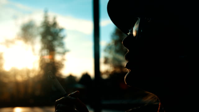 Gorgeous cinematic close up slow motion shot of a female silhouette smoking a cigarette
