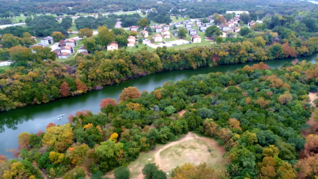 vídeos de stock e filmes b-roll de gorgeous colorful green fall autumn along colorado river with homes and neighborhood along nature and water austin , texas - town