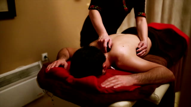 gorgeous dark-haired young man on a hot rocks neck massage - massage room stock videos & royalty-free footage