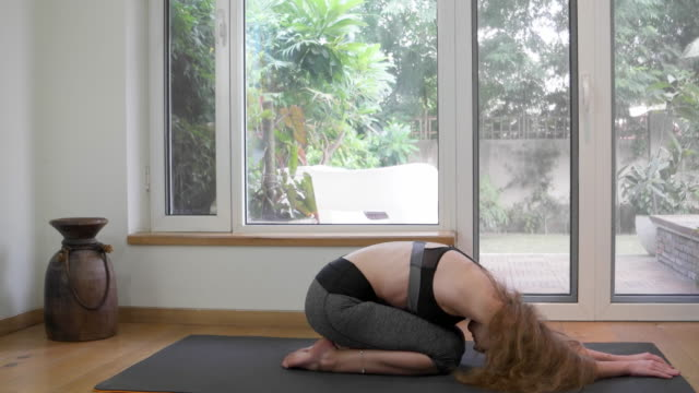 gorgeous fit woman stretching herself on a yoga mat performing in various positions - kneeling stock videos and b-roll footage