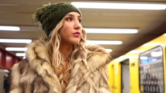 gorgeous girl at a subway station - pelliccia materiale tessile video stock e b–roll
