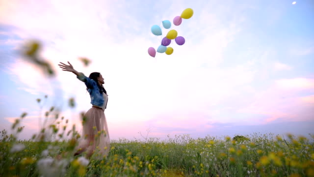 gorgeous girl in denim jacket letting go of balloons - simple living stock videos & royalty-free footage