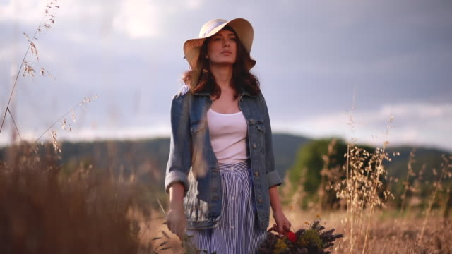 Gorgeous girl in denim jacket walking through a golden meadow field