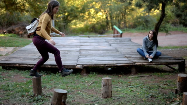 gorgeous girl playing with her sister in the woods - capanna di legno video stock e b–roll
