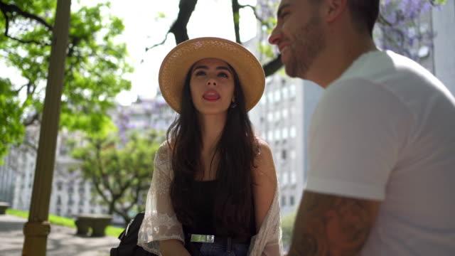 公園でリラックスしながら、彼女のボーイフレンドと話すゴージャスな女の子 - キャンパス点の映像素材/bロール