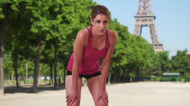 gorgeous healthy young white jogger posing near eiffel tower in paris - out of breath stock videos and b-roll footage