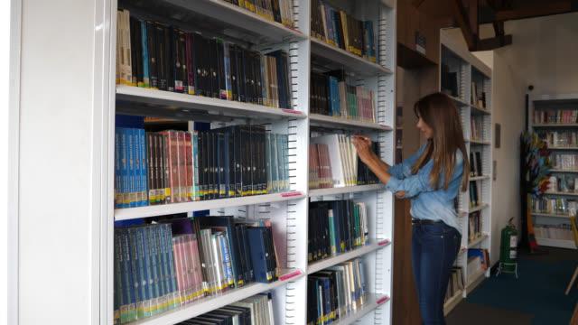 vidéos et rushes de magnifique étudiante d'amérique latine à la recherche d'un livre dans une bibliothèque publique - rayonnage de livre
