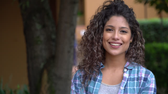 gorgeous latin american student with curly hair looking at camera smiling - university student stock videos & royalty-free footage