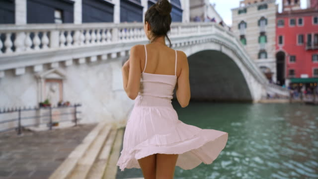 Gorgeous Latina tourist in sundress relaxes by Grand Canal
