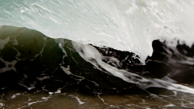 Gorgeous lip of wave that looks like a thin sheet of glass gliding into the camera on the shallow sand beach in the California summer sun. Shot in slowmo on the Red Dragon at 300FPS.