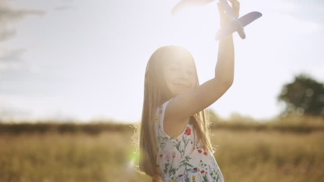 gorgeous little girl playing in meadow with her airplane model at sunset.slow-motion - model aeroplane stock videos & royalty-free footage