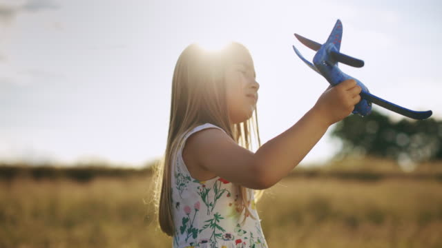 gorgeous little girl playing in meadow with her airplane model at sunset.slow-motion - pilot stock videos & royalty-free footage