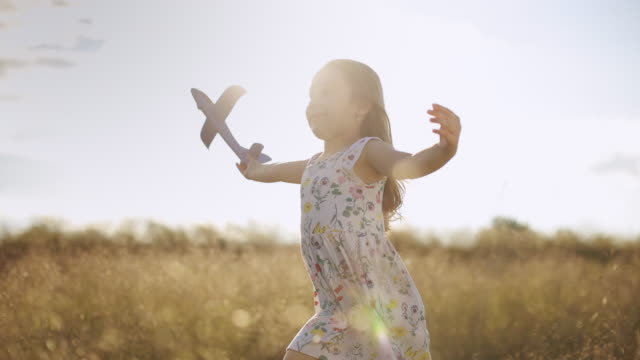 gorgeous little girl running in meadow with her airplane toy at sunset. slow motion - model aeroplane stock videos & royalty-free footage