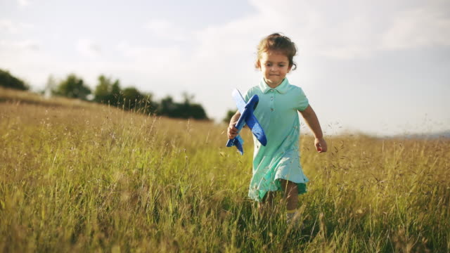 gorgeous little toddler girl running in meadow with her airplane toy at sunset. slow motion - model aeroplane stock videos & royalty-free footage
