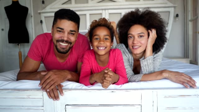 gorgeous mixed race family in bed - perfection stock videos & royalty-free footage