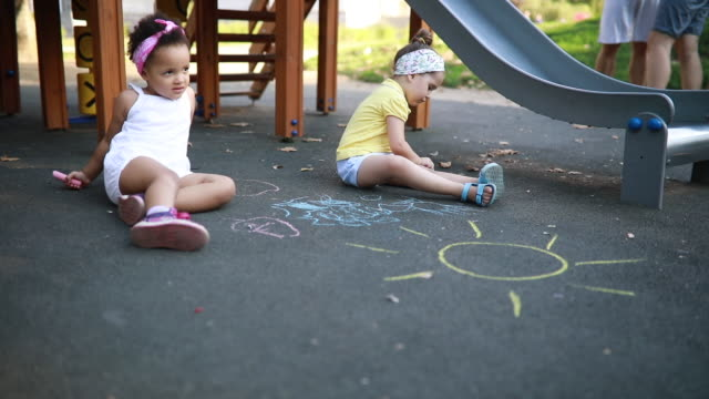 gorgeous mixed race toddlers drawing with chalk on a playground - gessetto da lavagna video stock e b–roll