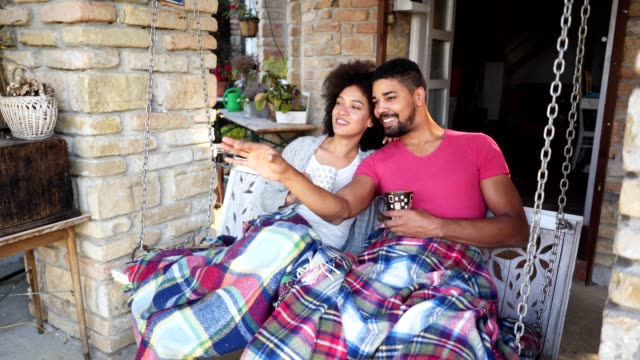 gorgeous romantic couple swinging on a porch swing - cozy stock videos & royalty-free footage