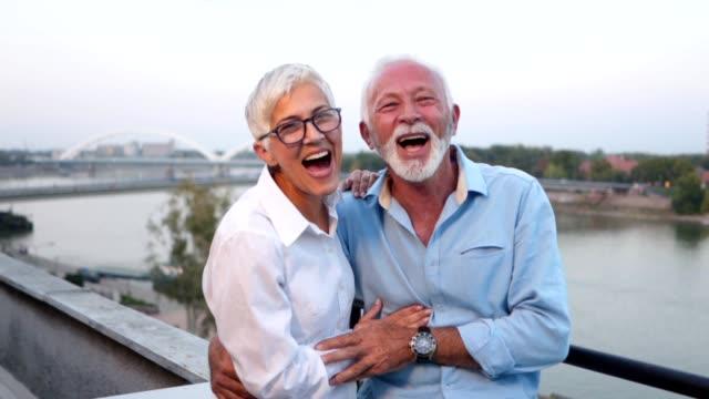 wunderschöne senior paar genießen ihre zeit auf ein geselliges beisammensein - offenes lächeln stock-videos und b-roll-filmmaterial