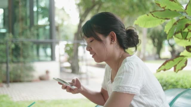 stockvideo's en b-roll-footage met prachtige lachende aziatisch meisje gebruik smartphone - ingesproken bericht