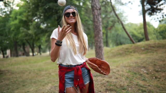 Gorgeous smiling girl playing baseball in nature