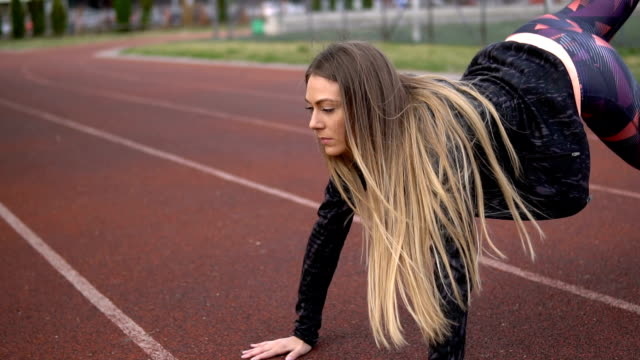 gorgeous sports woman exercising on a running track - leggings stock videos & royalty-free footage