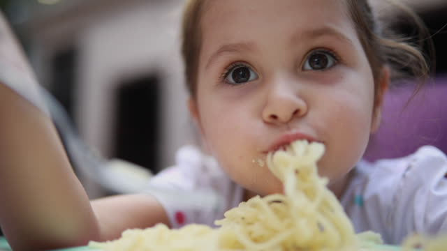 Gorgeous toddler girl eating spaghetti