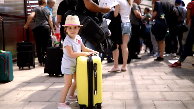 Gorgeous toddler waiting in line to board a plane